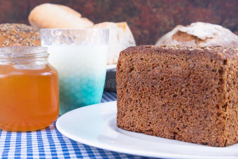Kleurrijke foto van een stuk van multigrainbrood gecombineerd met yoghurt en een kruik jam royalty-vrije stock afbeelding