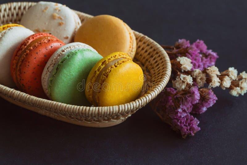 Kleurrijke Franse macaron of Italiaanse macaronstapel op mand Huis stock foto