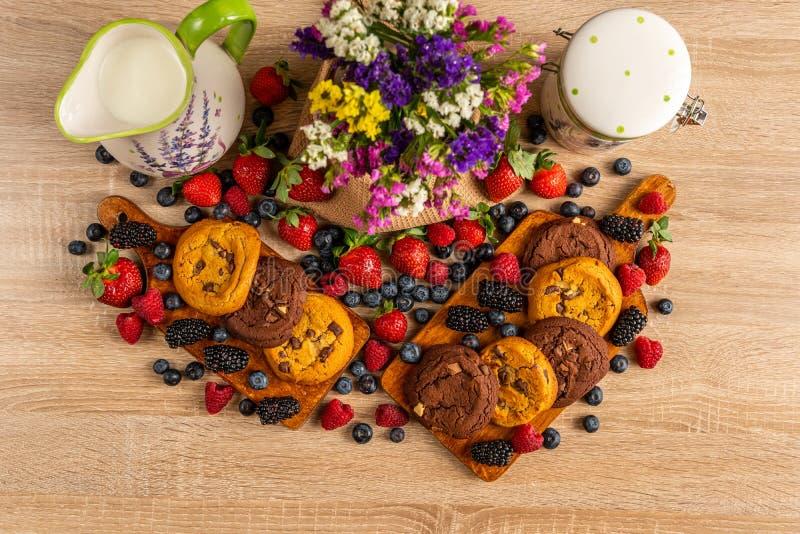 Kleurrijke geassorteerde mengeling van wilde bessen, bruine koekjes, melk en bloemen royalty-vrije stock afbeelding
