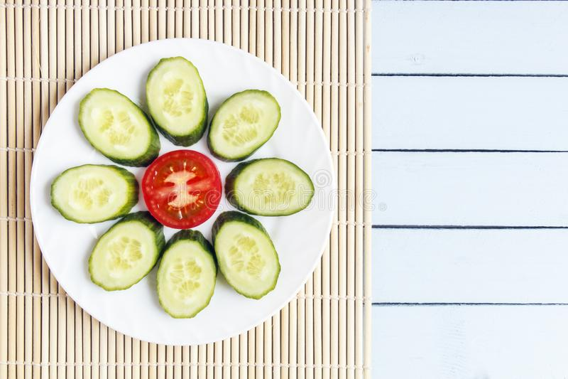 Kleurrijke gesneden verse organische groenten op bamboemat Rijpe tomaat en komkommer in vorm van bloem Hoogste mening over houten royalty-vrije stock foto's