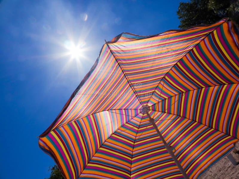 Kleurrijke gestreepte parasol tegen de hemel en de zon Heet weer Een strandvakantie royalty-vrije stock foto