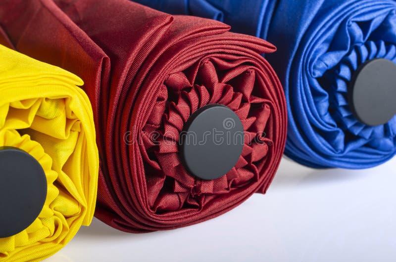 Kleurrijke gevouwen winddieparaplu's op wit worden ge?soleerd royalty-vrije stock foto