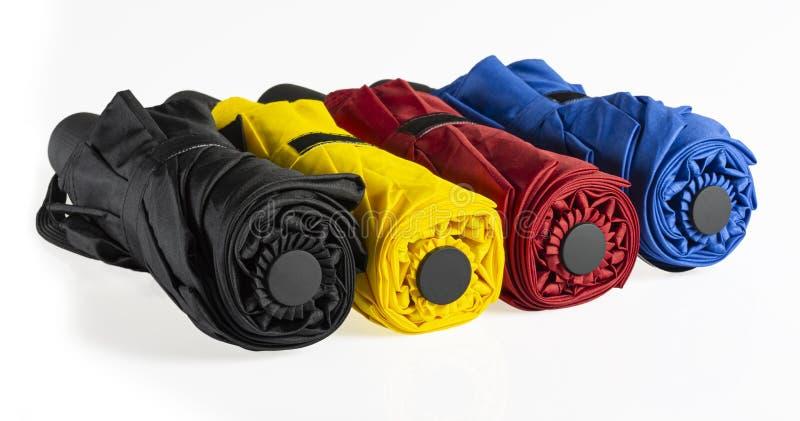 Kleurrijke gevouwen winddieparaplu's op wit worden ge?soleerd stock foto
