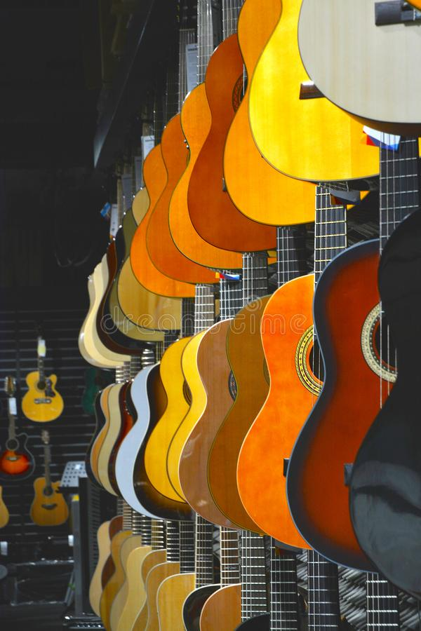 Kleurrijke gitaren in de winkel stock afbeelding