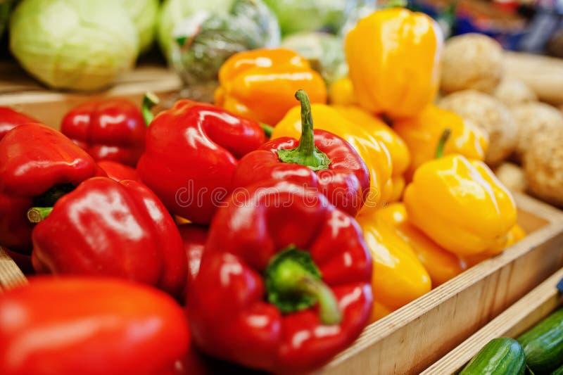 Kleurrijke glanzende verse groenten Klok zoete gele en Spaanse pepers op de plank van een supermarkt of kruidenierswinkelopslag royalty-vrije stock fotografie