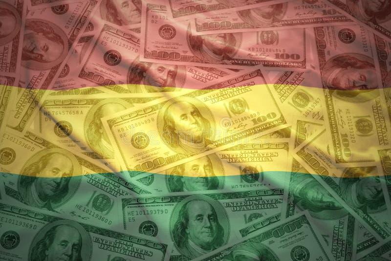 kleurrijke golvende Boliviaanse vlag op een achtergrond van het dollargeld stock fotografie