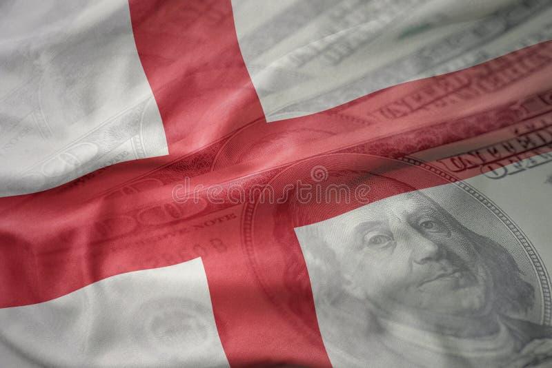 Kleurrijke golvende nationale vlag van Engeland op een Amerikaanse achtergrond van het dollargeld stock fotografie