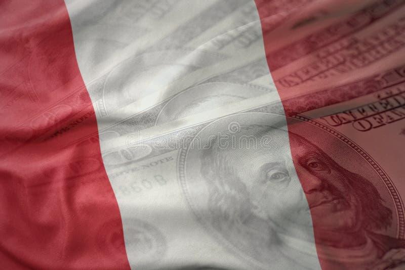 Kleurrijke golvende nationale vlag van Peru op een achtergrond van het dollargeld Het concept van financiën stock foto