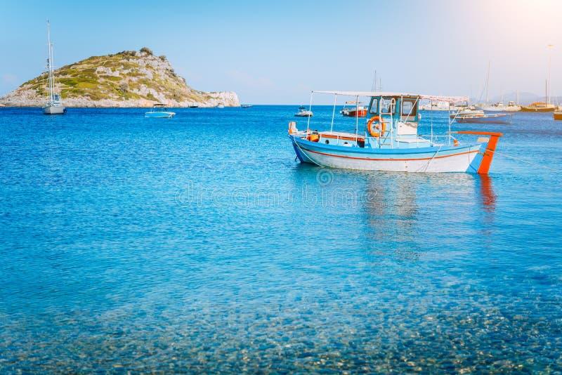 Kleurrijke Griekse vissersboot bij het kalme duidelijke water op de vroege zomerochtend Witte rots bij de achtergrond stock foto's