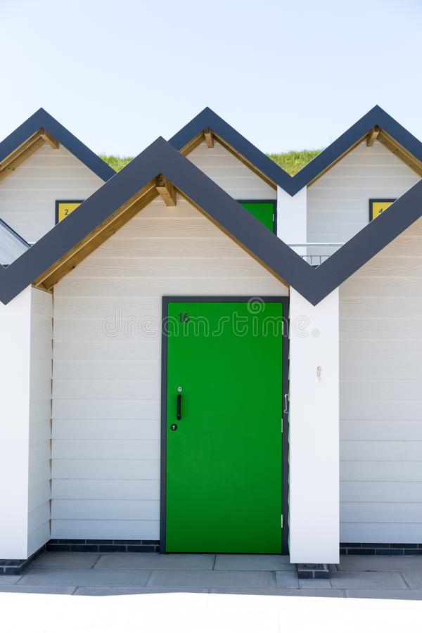 Kleurrijke groene deur, met elke één die, witte strandhuizen individueel worden genummerd op een zonnige dag stock fotografie