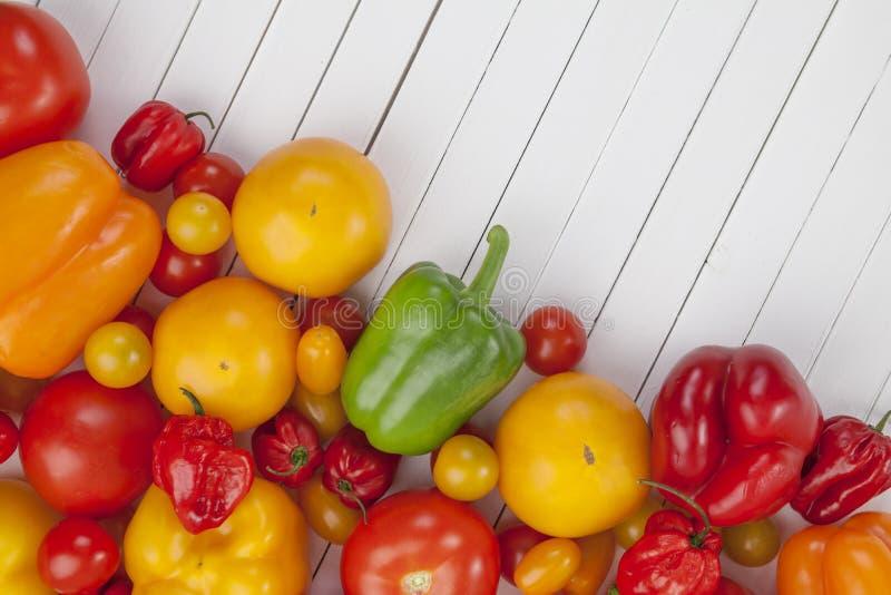 Kleurrijke groenten op witte houten achtergrond: tomaten en paprika, hoogste mening stock afbeeldingen
