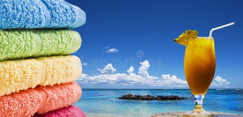 Kleurrijke handdoeken en een fruitcocktail op het strand royalty-vrije stock afbeeldingen