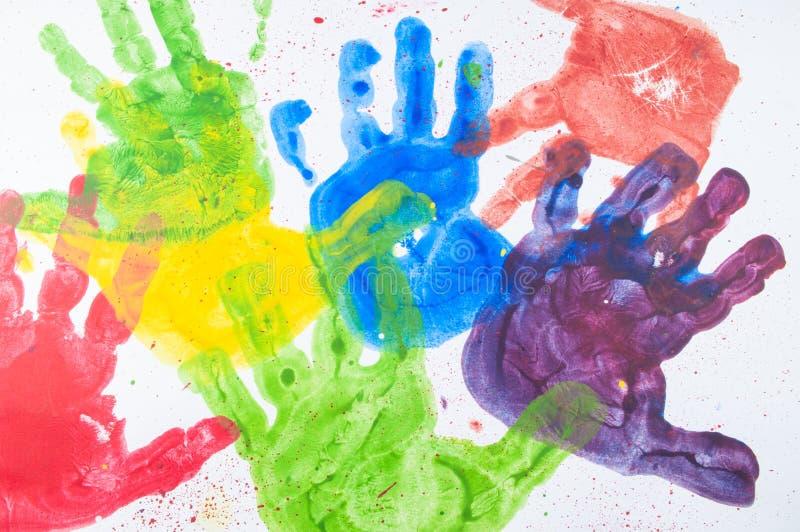 Kleurrijke handverf van jonge geitjeshanden op Witboek stock afbeelding