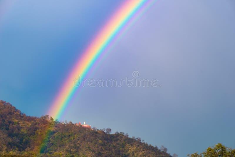 Kleurrijke heldere regenboog in de hemel Tempel op de heuvel stock foto