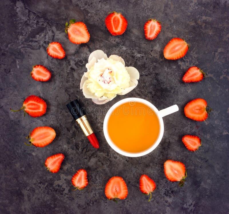 Kleurrijke heldere samenstelling van kop thee, aardbeien, lippenstift en pioenbloem royalty-vrije stock fotografie