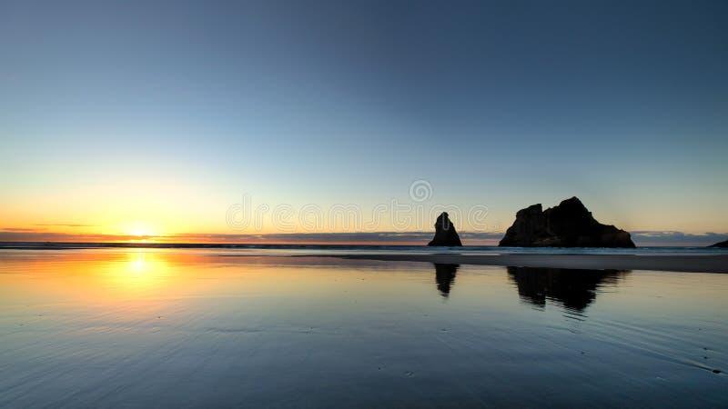 Kleurrijke hemel en bezinning bij Wharariki-strand, Nieuw Zeeland stock foto's