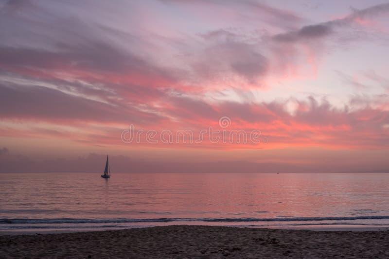 Kleurrijke hemel na Mallorcan-zonsondergang; zeilboot op roze overzees royalty-vrije stock foto's
