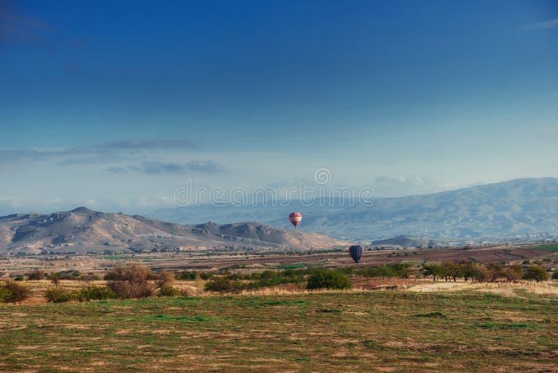 Kleurrijke hete luchtballons die over Rode vallei in Cappadocia vliegen, stock foto's
