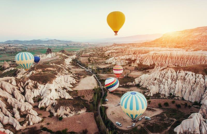 Kleurrijke hete luchtballons die over Rode vallei in Cappadocia vliegen, stock foto