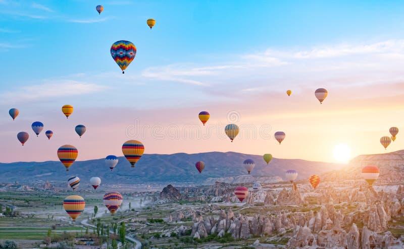 Kleurrijke hete luchtballons die over rotslandschap in Cappadocia Turkije vliegen stock foto's