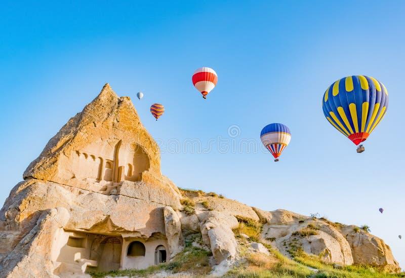 Kleurrijke hete luchtballons die over rotslandschap in Cappadocia Turkije vliegen stock foto