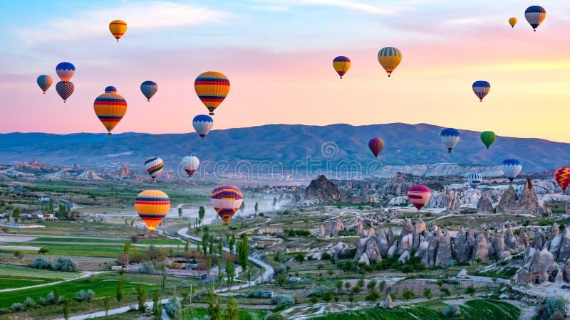Kleurrijke hete luchtballons die over rotslandschap in Cappadocia Turkije vliegen royalty-vrije stock foto's
