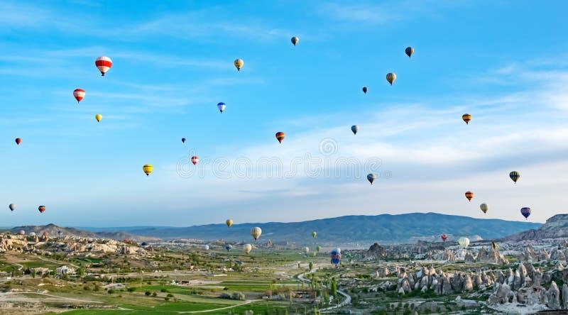 Kleurrijke hete luchtballons die over rotslandschap in Cappadocia Turkije vliegen royalty-vrije stock fotografie