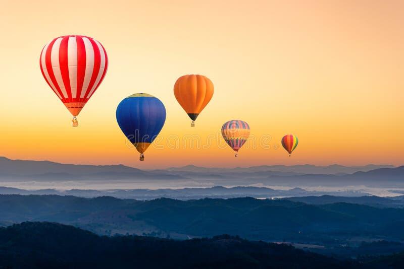 Kleurrijke heteluchtballonnen die over de berg vliegen stock fotografie