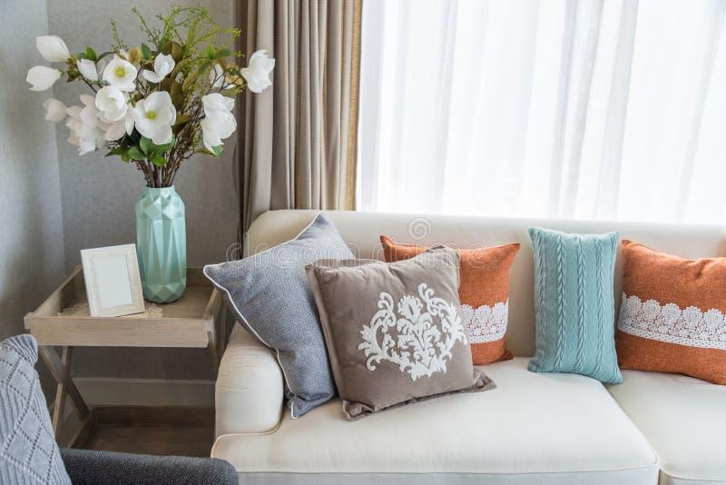 Kleurrijke hoofdkussens op beige bank met bloemen in woonkamer royalty-vrije stock foto