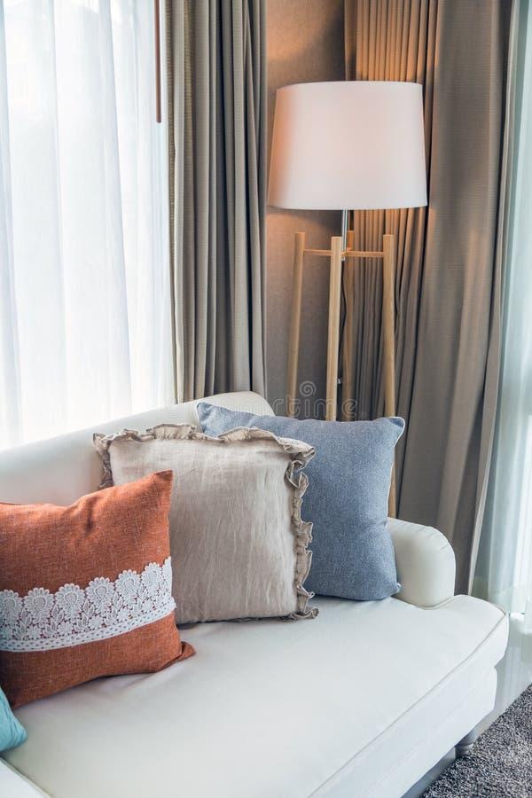 Kleurrijke hoofdkussens op beige bank met lamp in woonkamer royalty-vrije stock foto