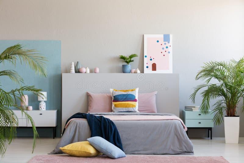 Kleurrijke hoofdkussens op tapijt naast bed in moderne grijze slaapkamer binnen royalty-vrije stock foto's