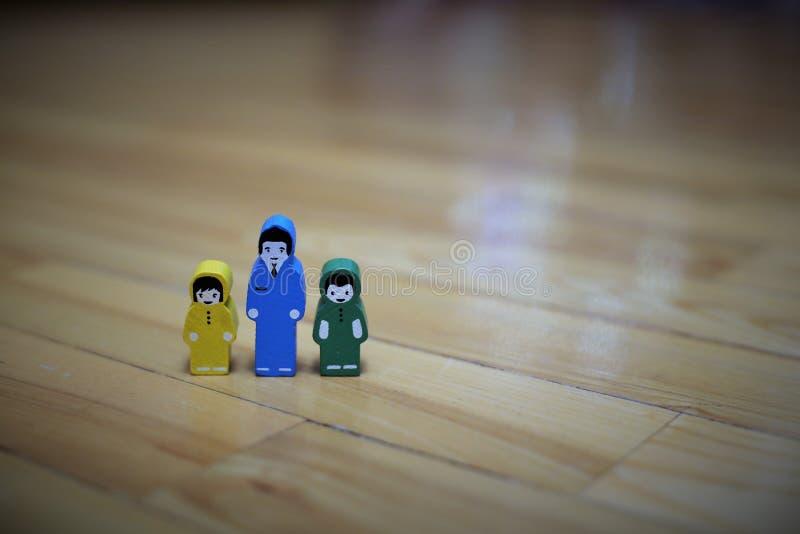 Kleurrijke houten cijfers van de vader en de dochter met de zoon op de achtergrond van de houten vloer stock foto