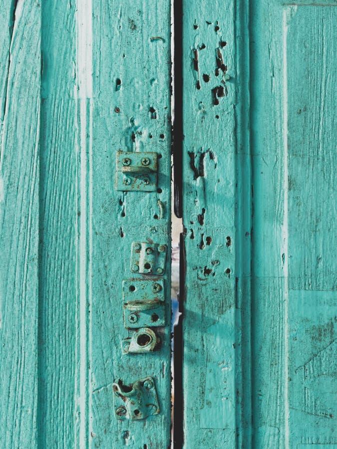 Kleurrijke houten die deuroppervlakte met slot met groene, blauwe, of aquamarijnkleur wordt geschilderd in uitstekende en retro s stock fotografie