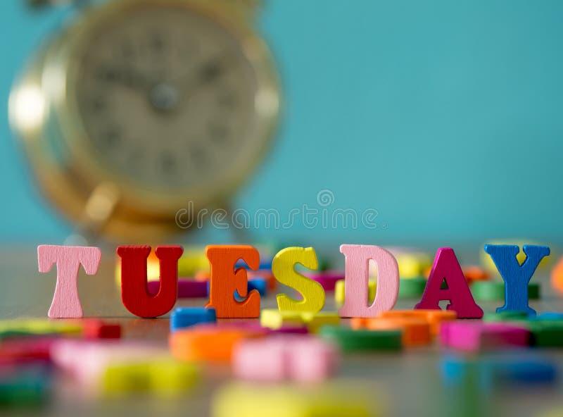 Kleurrijke houten woorddinsdag op houten lijst en uitstekende wekker royalty-vrije stock foto
