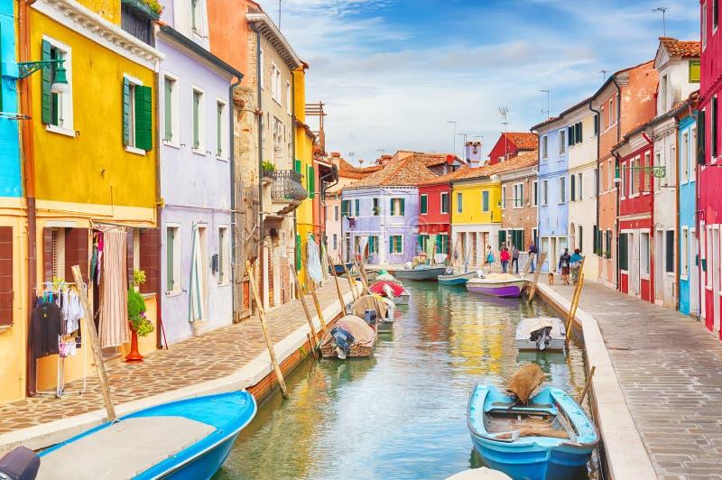 Kleurrijke huizen met boten in Burano-eiland met bewolkte blauwe hemel dichtbij Venetië, Italië Populaire en beroemde toeristenpl stock foto's