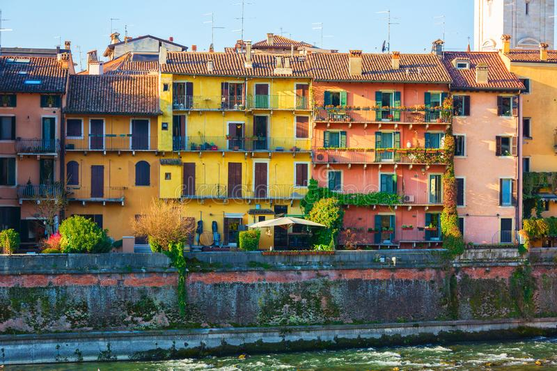 Kleurrijke huizenvoorgevels dichtbij de Adige-rivierbank, Verona, Italië stock foto