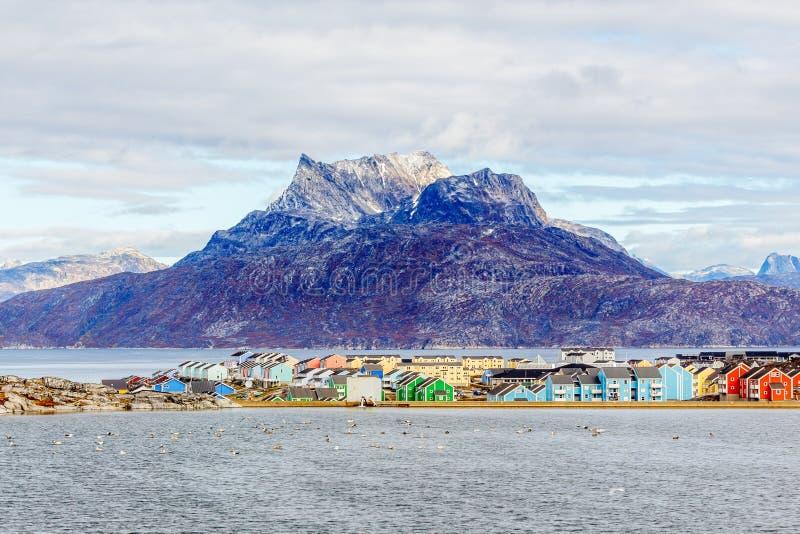 Kleurrijke Inuit-gebouwen in woondistrict van Nuuk-stad met meer in de voorgrond en sneeuwpiek van Sermitsiaq-berg, royalty-vrije stock foto