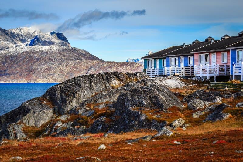 Kleurrijke Inuit-huizen onder de rotsen en zware stenen met Serm royalty-vrije stock afbeeldingen