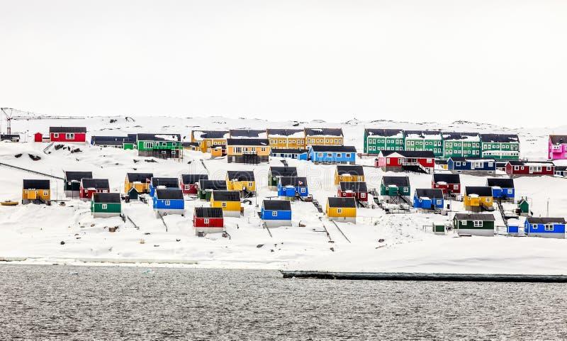 Kleurrijke Inuit-huizen op sneeuwheuvel, Aasiaat-stad stock afbeelding