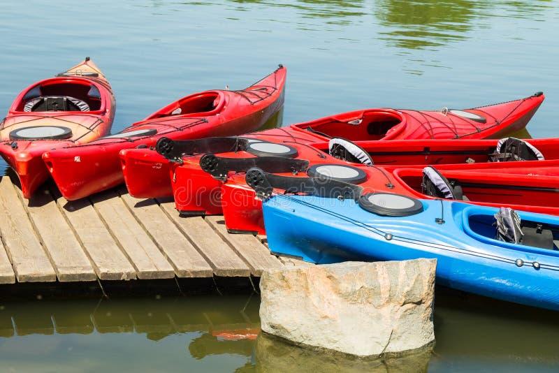 Kleurrijke kano's en kajaks die op de pier liggen royalty-vrije stock afbeelding
