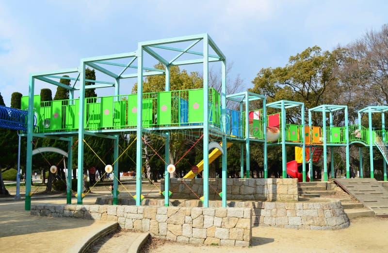 Kleurrijke kinderenspeelplaats in openbaar park in de stad, onder s stock afbeelding