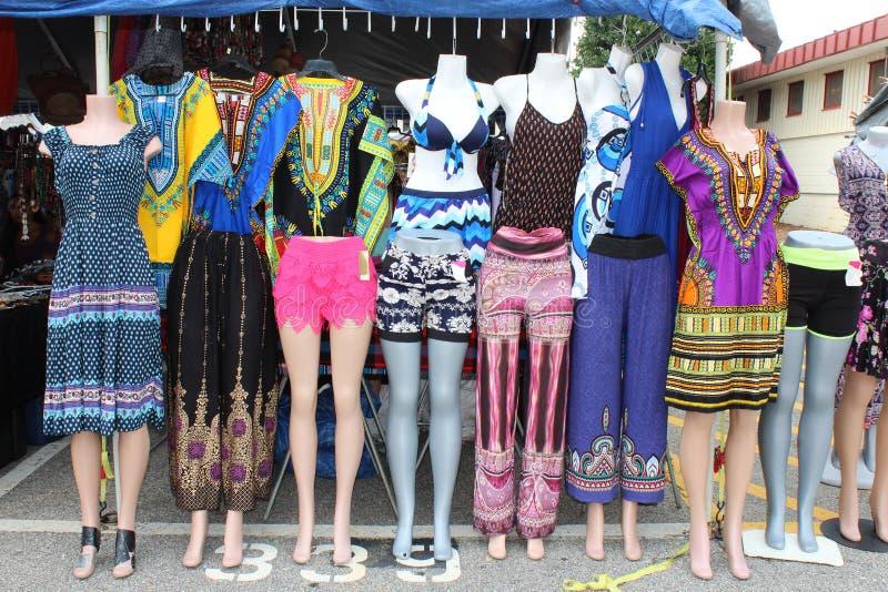 Kleurrijke kleding en broek op ledenpoppen bij een openluchtvlooienmarkt stock fotografie
