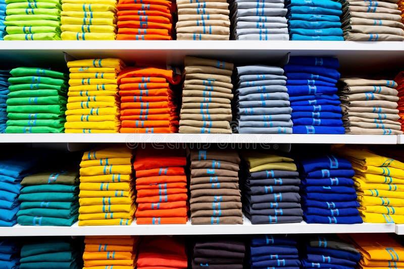 Kleurrijke kleding keurig op planken stock afbeelding