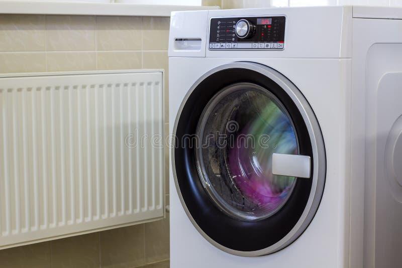 Kleurrijke kleren en handdoeken in wasmachine stock foto