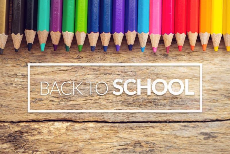 Kleurrijke kleurenpotloden op oude houten lijst als achtergrond met tekst terug naar school in wit grenskader royalty-vrije stock fotografie