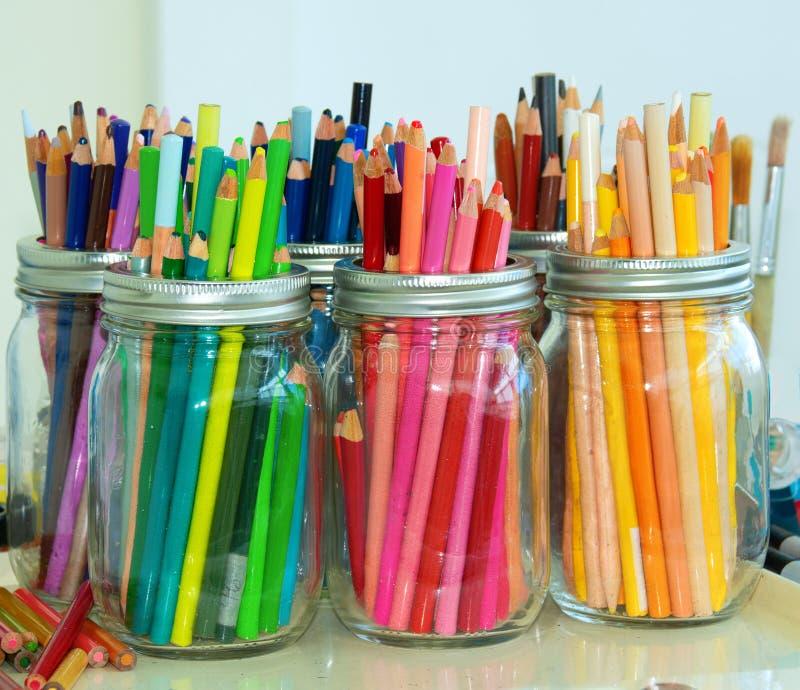 Kleurrijke kleurpotloden in glaskruiken stock foto's