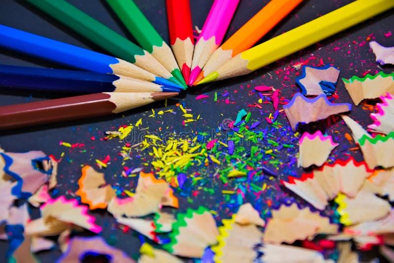 Kleurrijke kleurpotloden met kleurrijke spaanders op een zwarte achtergrond royalty-vrije stock fotografie