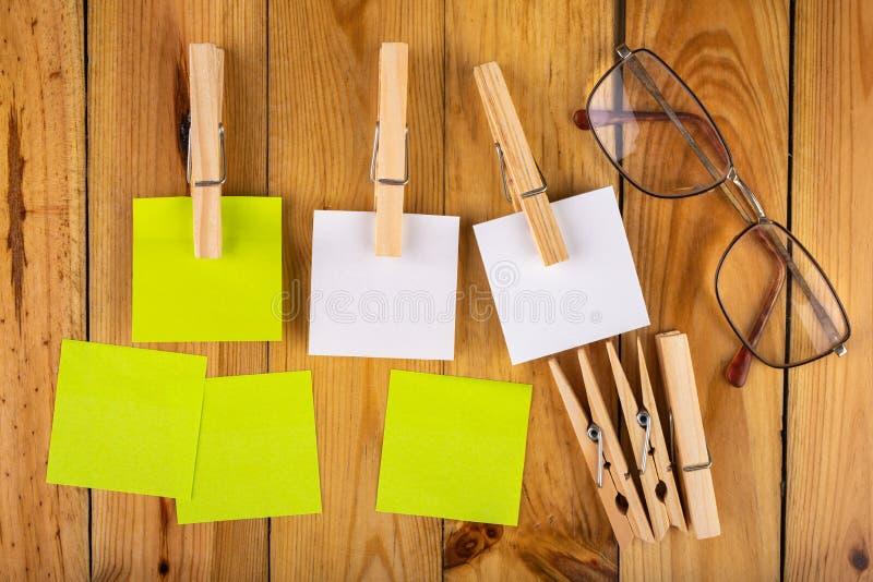 Kleurrijke kleverige die nota's op houten klemmen worden gehangen Kleverige nota's voor besparingsherinneringen op een houten lij royalty-vrije stock afbeelding