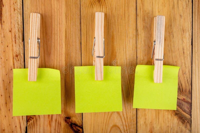 Kleurrijke kleverige die nota's op houten klemmen worden gehangen Kleverige nota's voor besparingsherinneringen op een houten lij royalty-vrije stock fotografie