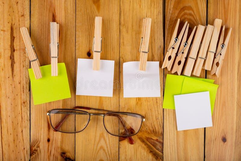 Kleurrijke kleverige die nota's op houten klemmen worden gehangen Kleverige nota's voor besparingsherinneringen op een houten lij stock afbeelding